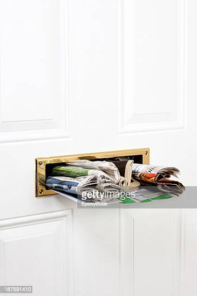 A mail slot stuffed with mail and newspapers, close-up