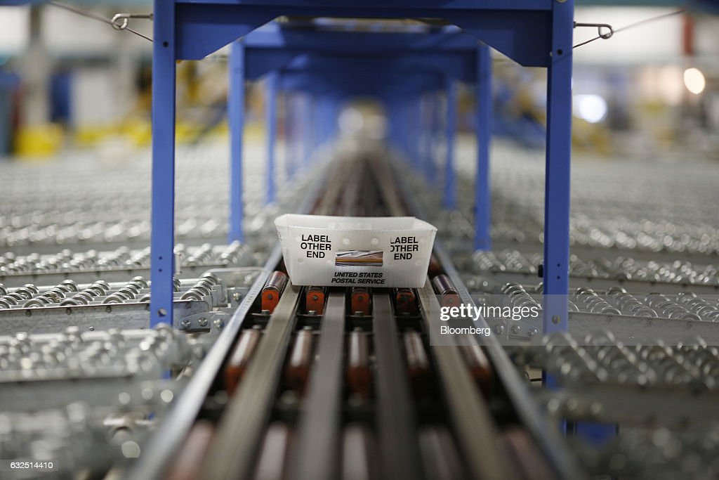 A mail tray moves along an automated sorting machine inside a United States Postal Service (USPS) sorting center in Louisville, Kentucky, U.S., on Friday, Jan. 13, 2017. Starting January 22, the cost of mailing a one-ounce first-class letter will return to being 49 cents, up from 47 cents, where it had been since April. Photographer: Luke Sharrett/Bloomberg via Getty Images
