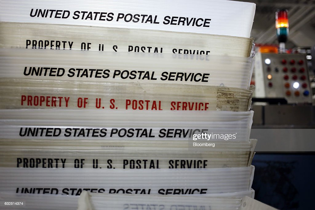 Mail trays sit stacked beside an automated sorting machine at the United States Postal Service (USPS) sorting center in Louisville, Kentucky, U.S., on Friday, Jan. 13, 2017. Starting January 22, the cost of mailing a one-ounce first-class letter will return to being 49 cents, up from 47 cents, where it had been since April. Photographer: Luke Sharrett/Bloomberg via Getty Images