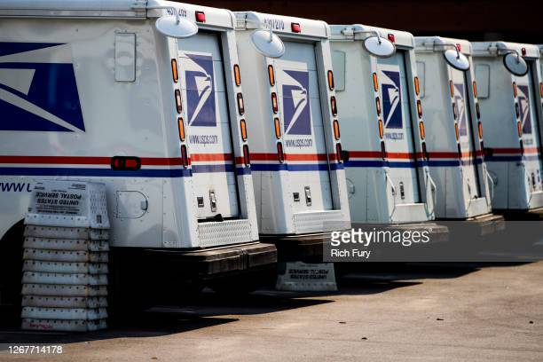 Mail trucks are seen as rally goers gather at a post office to protest the Trump administration's handling of the US Postal System at the Rally to...