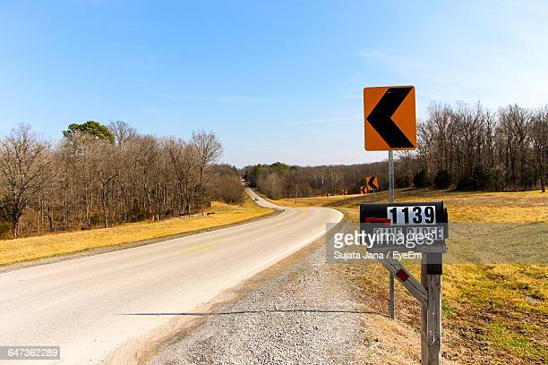 mailbox and arrow signs on field by empty road against clear sky - curved arrows stock photos and pictures