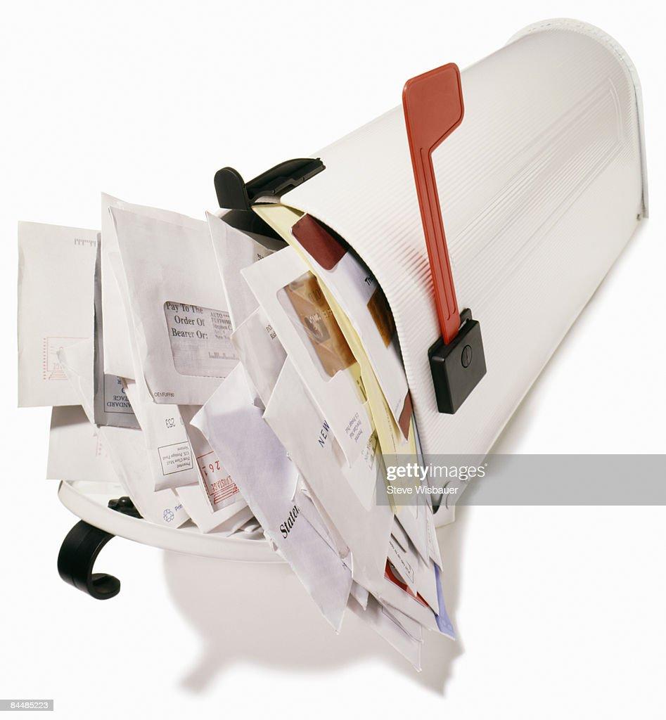 Mailbox stuffed overflowing with bills,  junk mail : Stock Photo