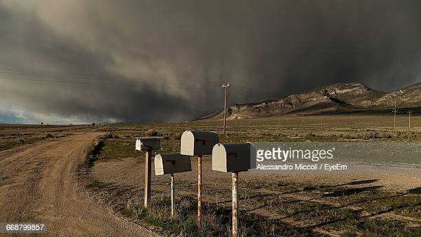 mailboxes in row on dirt road at countryside landscape - alessandro miccoli stockfoto's en -beelden