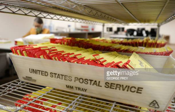 Mail-in ballots sit in containers from the US Postal Service waiting to be processed by election workers at the Salt Lake County election office in...