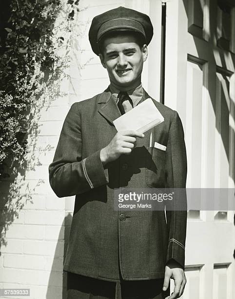 Mailman holding blank form outdoors, (B&W), portrait