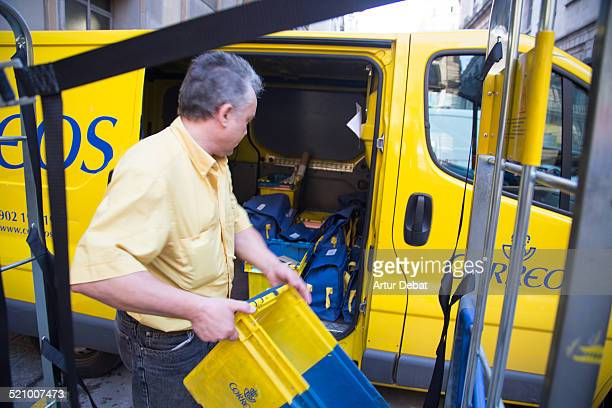 Mailman preparing his yellow van for spread the mail to the costumers with the Spanish mail company of Correos in the Barcelona city Catalonia Europe