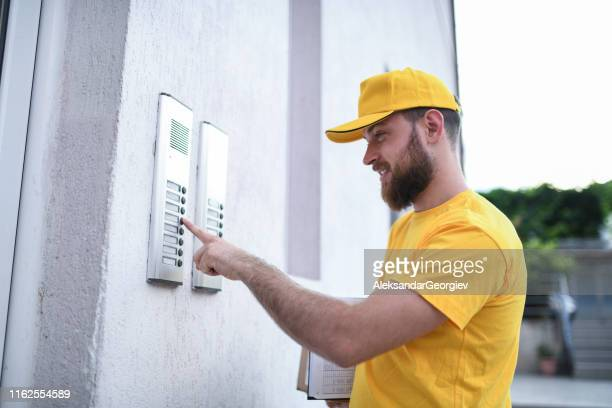 mailman ringing the bell to deliver a package - ringing doorbell stock pictures, royalty-free photos & images