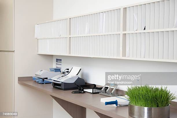 Mailroom in office with counter, fax, postal meter and mail slots