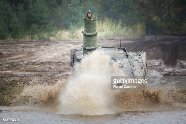 Main battle tank 'Leopard2' with attached diving shaft in which a soldier stands drives into a moat Shot during an exercise of the land forces on...