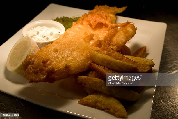 A main course dish of fish and chips in Lancaster Bomber beer batter served at the Millstone restaurant and hotel in Mellor Lancashire one of the...