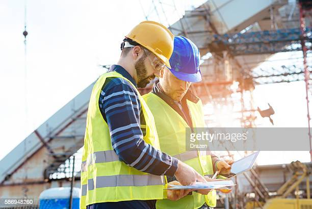 main engineer showing report to contractor at construction site - bridge built structure stock pictures, royalty-free photos & images
