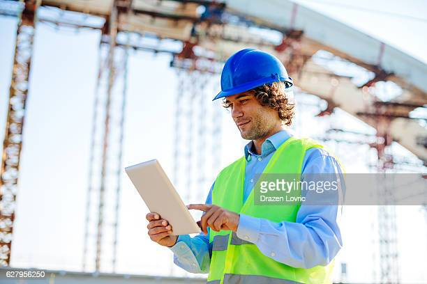 main engineer with digital tablet near bridge construction - bridge built structure stock photos and pictures