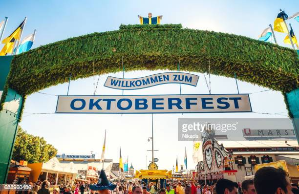 main entrance gate to oktoberfest fairground in munich, germany - entrance sign stock photos and pictures