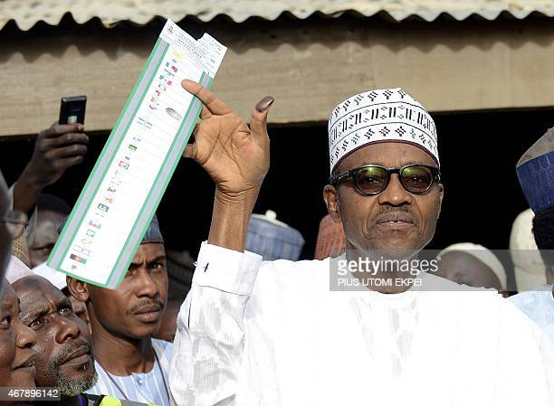Main opposition All Progressives Congress presidential candidate Mohammadu Buhari holds his ballot paper prior to casting his vote at a polling...