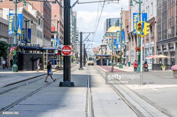 main street of downtown buffalo with cable car bus coming during summer day - buffalo new york state stock pictures, royalty-free photos & images