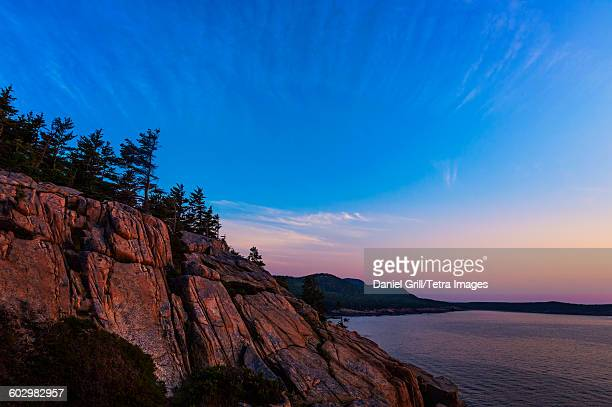 USA, Maine, Acadia National Park, Rocky cliff by sea at sunrise