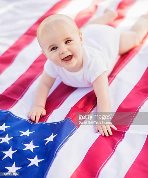 USA, Maine, Camden, Baby boy (6-11 months) lying on American flag