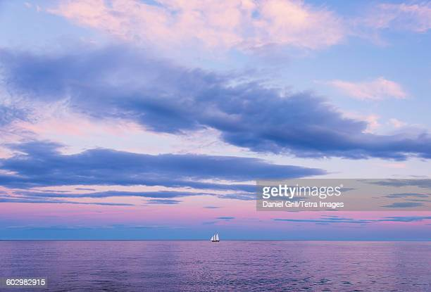 USA, Maine, Camden, Pastel-colored sunset seascape with sailboat