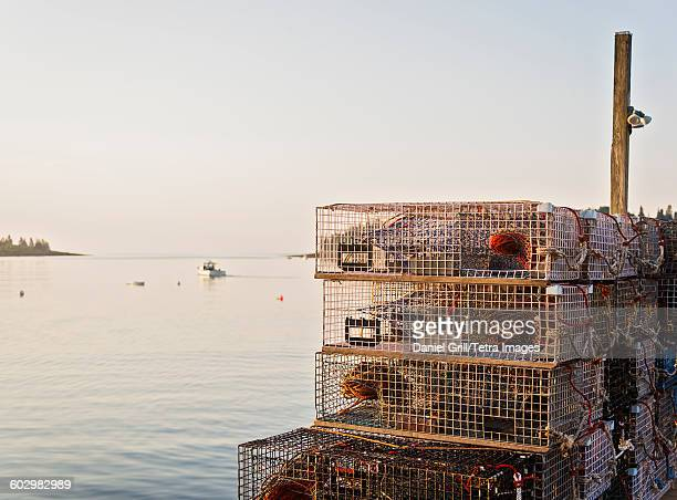 USA, Maine, St. George, Stacks of lobster traps by sea at sunrise