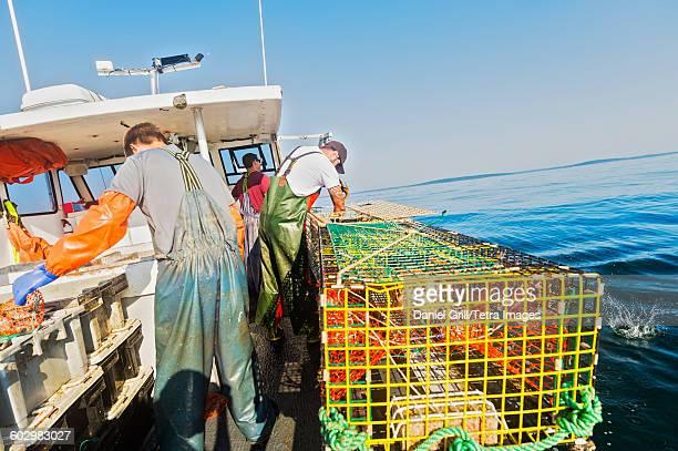 USA, Maine, St. George, Three fishermen working on boat