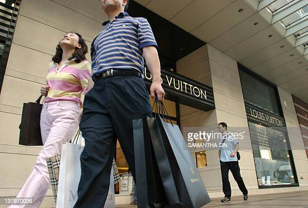 STORY 'AFPLIFESTYLEASIALUXURYHONG KONGCHINA' Mainland Chinese tourists loaded with shopping bags walk past a designer brand shop in the Tsim Sha Tsui...