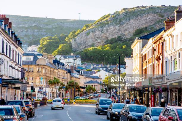 mainstreet in llandudno town with great orme head cliff in the background - llandudno wales stock pictures, royalty-free photos & images