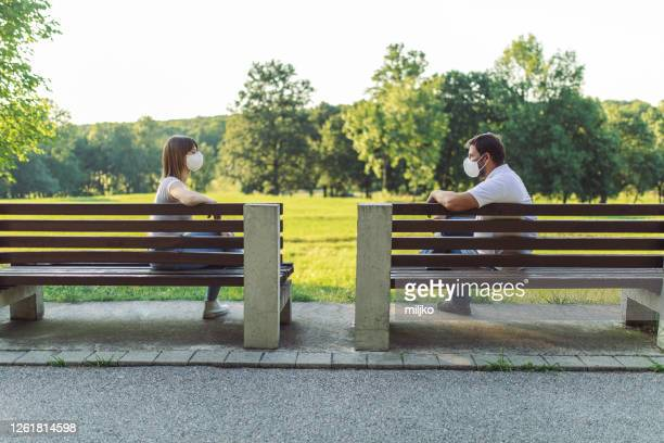 maintaining social distance in a public place - park bench stock pictures, royalty-free photos & images