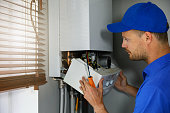 maintenance and repair service engineer working with house gas heating boiler