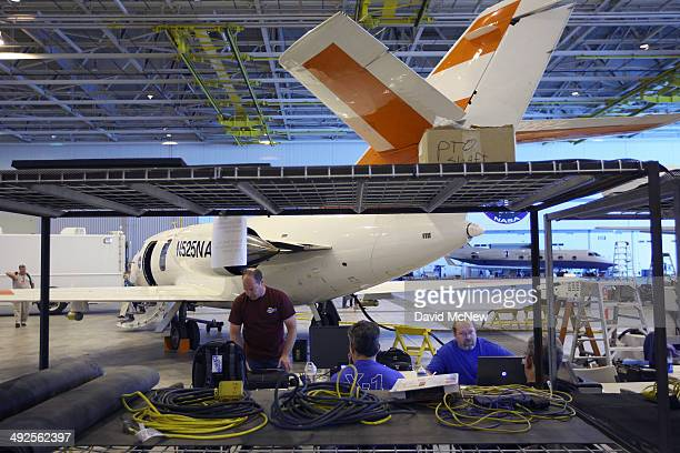 A maintenance crew works next to the NASA Langley HU25C jet used in research missions involved in the Alternative Fuel Effects on Contrails and...
