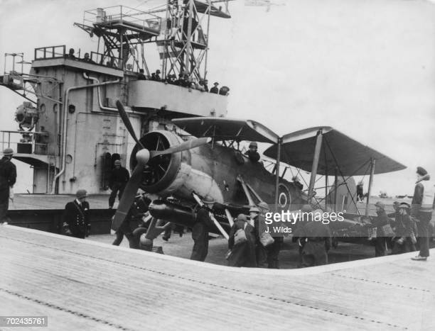 Maintenance crews bring a torpedoloaded Fairey Swordfish biplane torpedo bomber of 835 Squadron Fleet Air Arm by hydraulic lift onto the flight deck...