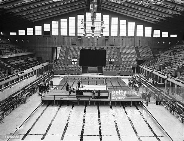 Maintenance crews preparing the boxing ring and officials' seating which are mounted over the swimming pool on a special platformat the Empire Pool...