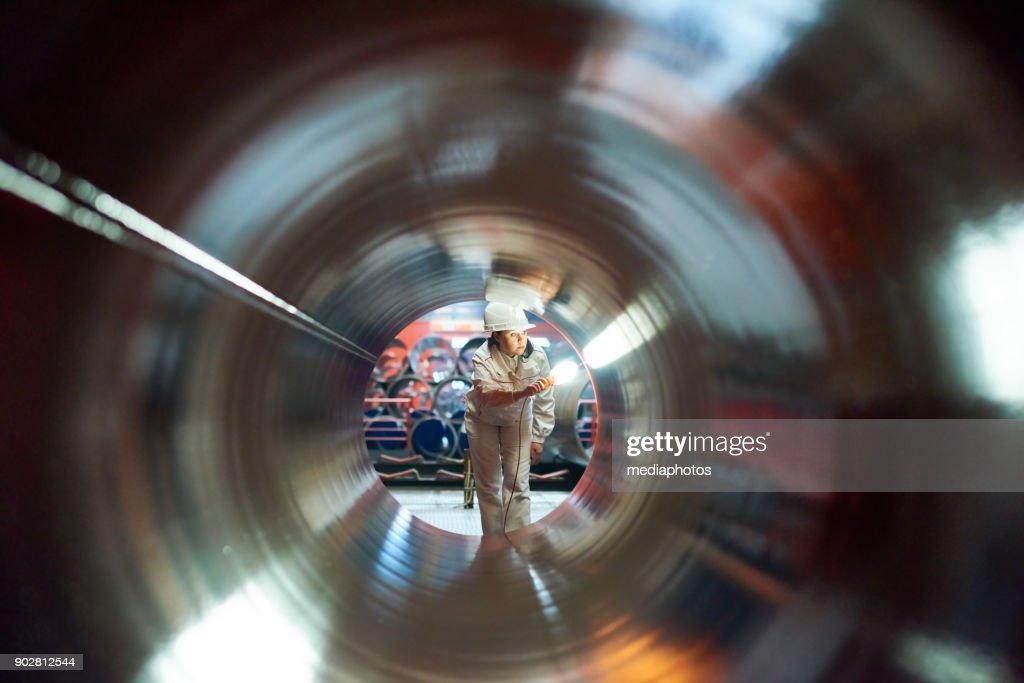 Maintenance engineer examining quality of tube : Stock Photo