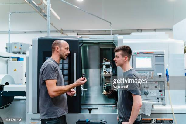maintenance engineer giving instruction to coworker while standing against machinery at industry - showing stock-fotos und bilder