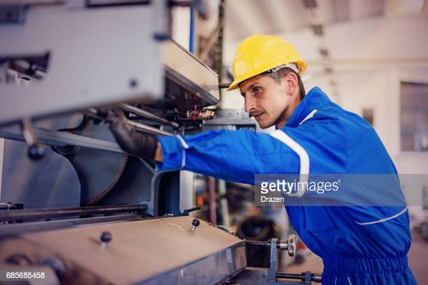 Maintenance engineer in factory checking cog wheels on machinery