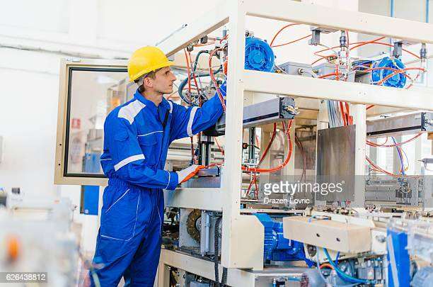 Maintenance engineer in factory installing the engine