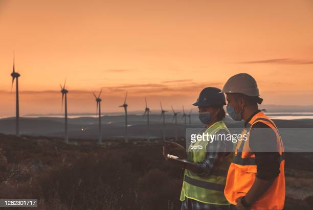maintenance engineer team with face mask working in wind turbine farm at sunset during pancemic - middle east stock pictures, royalty-free photos & images