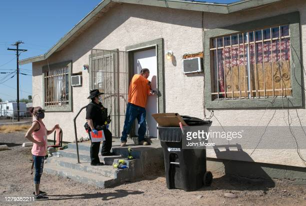 Maintenance man breaks the lock of a house as Maricopa County constable Darlene Martinez serves an eviction order on October 1, 2020 in Phoenix,...