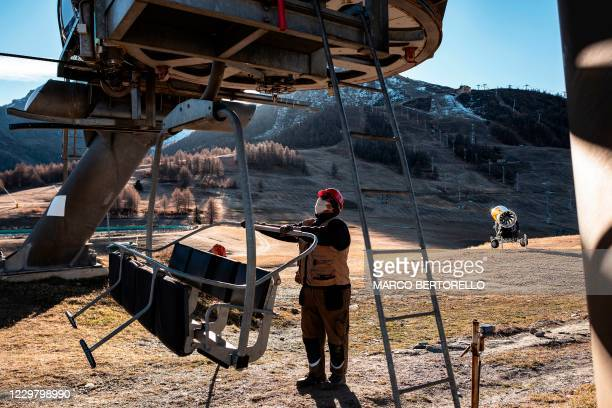 Maintenance man checks a chairlift at the alpine ski resort of Sestriere in Val Susa, Piedmont, Italy, on November 26, 2020 during the COVID-19...
