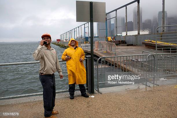 Maintenance men at One Brooklyn Bridge Plaza apartments Edwin Delvalle and Albert Macho monitor open windows in the apartment building along the East...