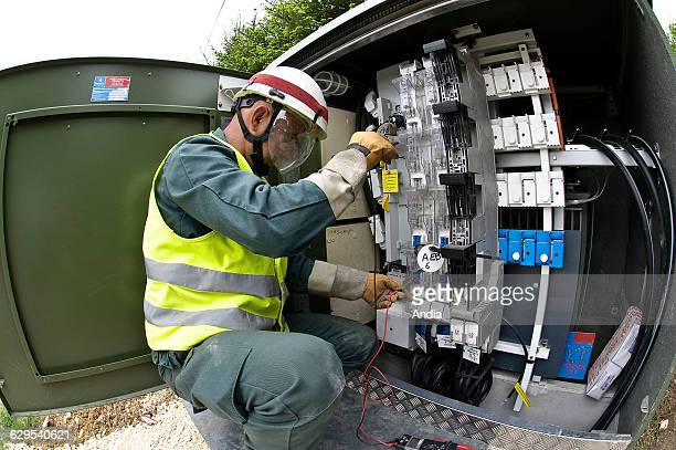 Maintenance of an electrical equipment box by a subcontractor worker equipped with a hard hat and a fluorescent yellow vest