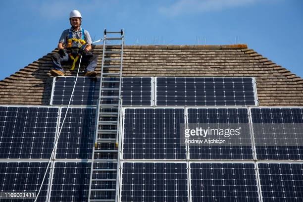 A maintenance person uses a ladder and harnesses to install equipment around a Solar panel array on the roof of a house to stop birds nesting...