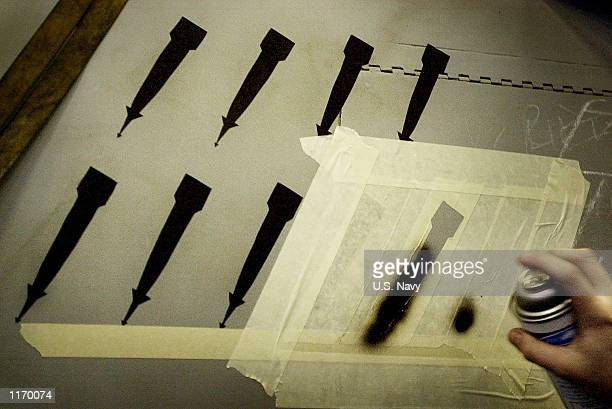 Maintenance personnel paint silhouettes of bombs on the fuselage of a Navy F/A18 'Hornet' signifying successful bombing missions over Afghanistan...