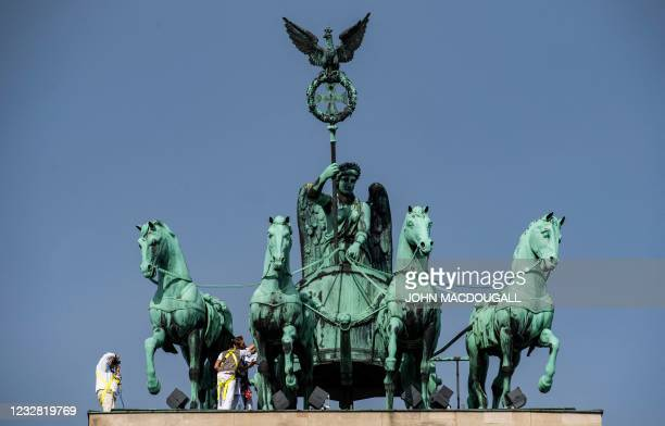 Maintenance specialists inspect one of the horses forming the Quadriga on top of Berlin's landmark Brandenburg Gate, on May 11, 2021. - Added to the...
