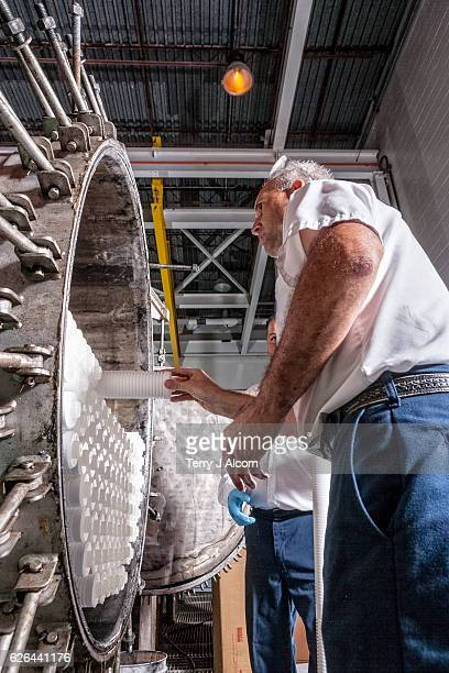 maintenance technician adding new water filters at filtration system - mineral water stock photos and pictures