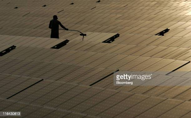 A maintenance worker cleans solar panels manufactured by Tata BP Solar India Ltd at North Delhi Power Ltd's Keshavpuram power station in New Delhi...