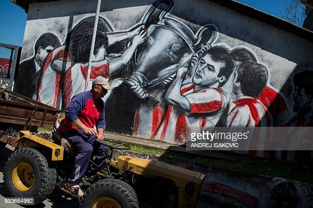 A maintenance worker drives past a mural at the Red Star Belgrade Marakana stadium on April 27 25 years after the Red Star Belgrade European Cup...