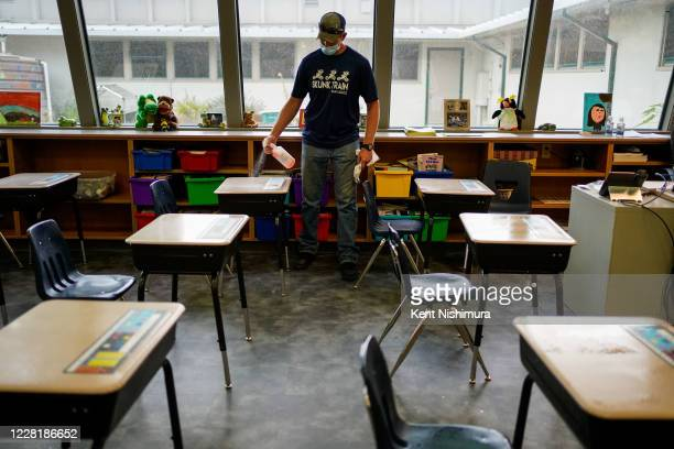 Maintenance worker KC Henderson sprays down student desks with rejuvnul disinfectant at Weaverville Elementary School on Monday Aug 17 2020 in...