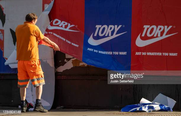 A maintenance worker removes posters depicting the Nike logo and reading 'Tory just do whatever you want' is removed from a wall in Shoreditch East...