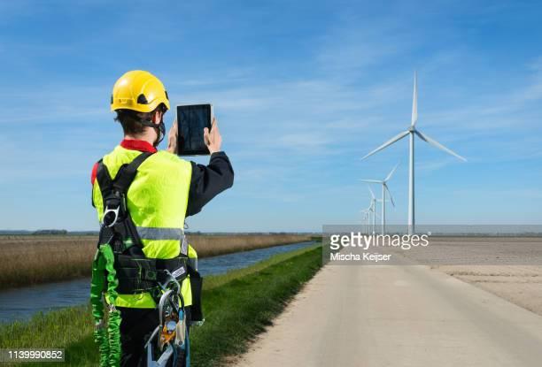 maintenance worker taking photography of wind farm using digital tablet, biddinghuizen, flevoland, netherlands - biddingshuizen stockfoto's en -beelden