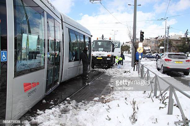 Maintenance workers and others assess the situation at the scene of a light rail car derailed by snow Jerusalem Israel February 20 2015